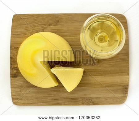 A photo of tetilla, a traditional Spanish soft cow milk cheese, with a slice cut off, and a glass of white wine, shot from above on white background