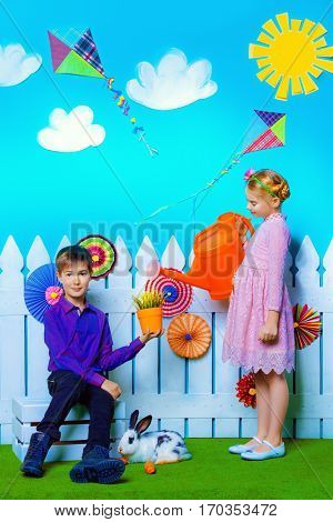 Two happy children play together in spring Easter decorations. Easter Bunny and painted eggs. Kid's fashion.