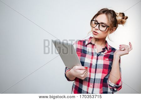 Woman in shirt and eyeglasses using tablet computer in studio. Isolated gray background