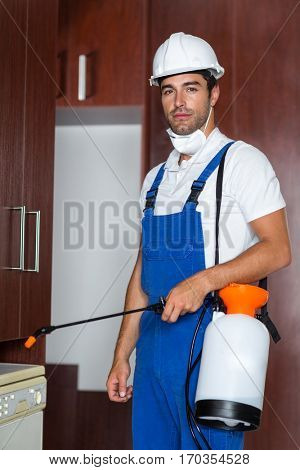 Portrait of confident pest worker holding sprayer in kitchen