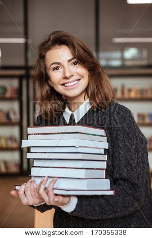 Happy student girl or young woman with stack of books in library
