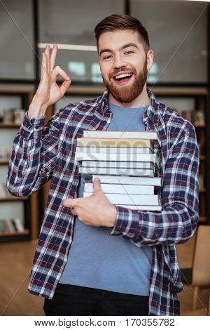 Portrait of a happy attractive man student holding books in library and showing okay gesture