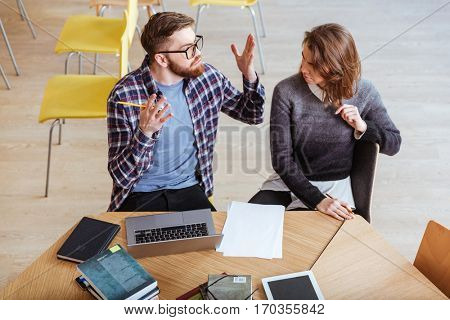 Irritated young couple working and arguing at the table together