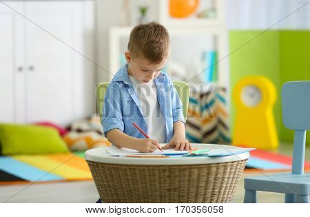 Little boy drawing picture at child psychologist's office