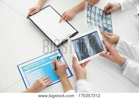 Team of doctors exploring lungs roentgenogram in clinic