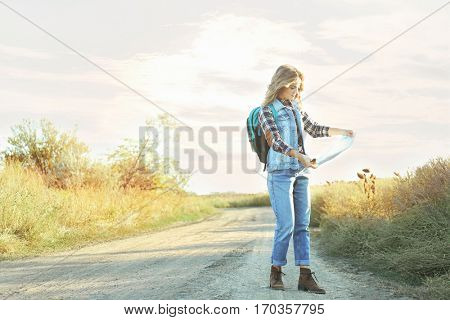 Beautiful young girl with map on countryside road