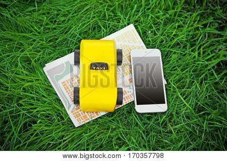Yellow toy taxi, phone with map on green grass