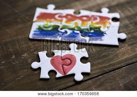 two pieces of a puzzle forming a heart and some other pieces forming a rainbow flag, on a rustic wooden surface