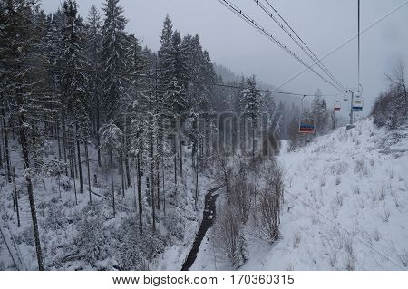 Chairlift with plastic bottles of water rises up in the mountains in winter