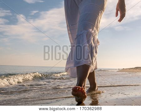 Closeup of woman wearing white skirt strolling barefooted along the beach