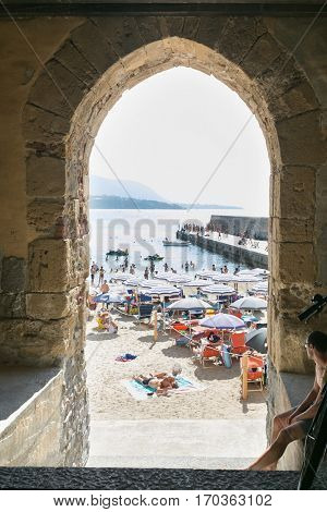 CEFALU,SICILY - JULY. 27. 2016: Unidentified people on sandy beach in Cefalu, Sicily, Italy at Sep 16, 2014. Cefalu is an attractive historic town and seaside resort.