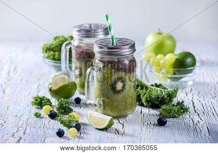 Green fresh detox vegan superfoods smoothie vitamins diet drink with kale chia seeds lime kiwi apple.