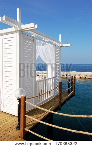 White beach tent on a background of blue sea in Turkish luxury hotel.