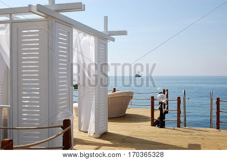 View of white beach tent ship and blue sea in Turkish luxury hotel.