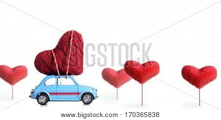 Blue retro toy car delivering craft heart for Valentine's day on white background