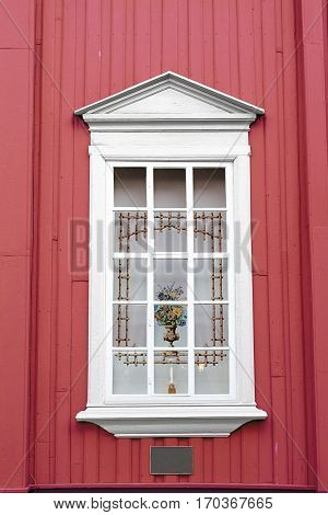 red wall white window curtain vase candle holder