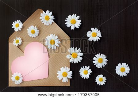 open paper envelope with the departing chamomiles on the table top view / emotional redolent letter