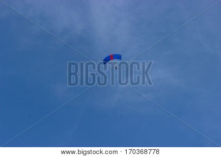 Airman is show parachuting on a bright sky day.