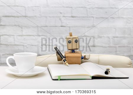 robot is sitting at the table working place: diary pens cups