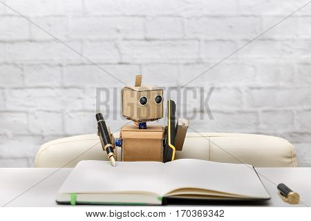 Robot writes in diary pen in black sitting at table
