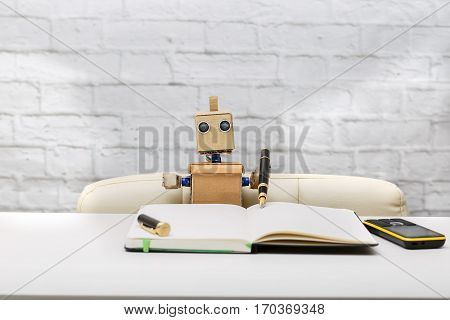 Robot writes in diary pen of black color the robot works