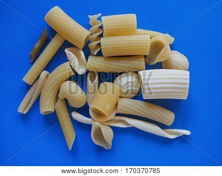 Many different types of Italian pasta including penne macaroni (maccheroni) fusilli spaghetti trenette (linguine) orecchiette tortiglioni conchiglie (shells) - blue background