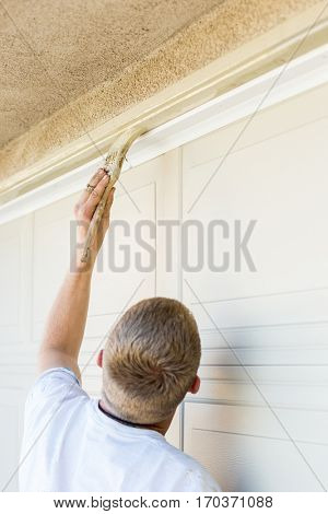 Professional Painter Cutting In With A Brush to Paint Garage Door Frame.