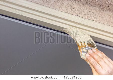 Professional Painter Cutting In With A Brush to Paint House Door Frame.