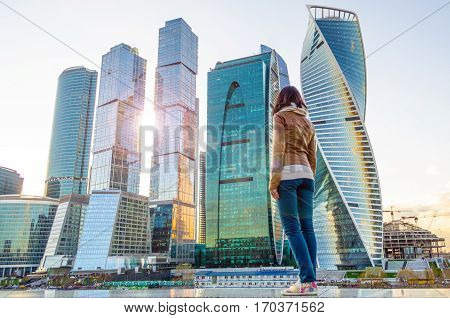 The girl looks at the sun and skyscrapers in the megalopolis