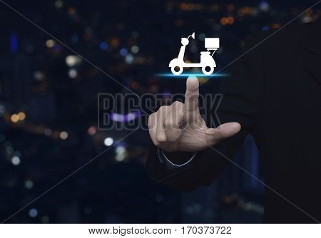 Businessman pressing motor bike icon over blur colorful night light city tower Business delivery service concept
