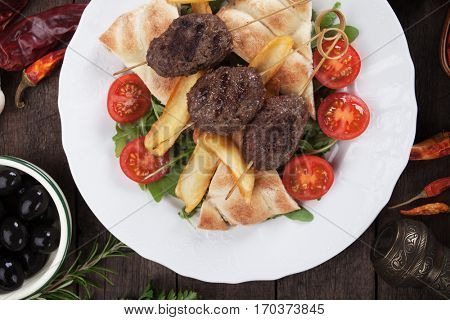 Turkish kofta kebab, minced meat skewer with fried potato and flatbread