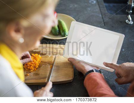 Senior Woman Cooking Food Kitchen Tablet