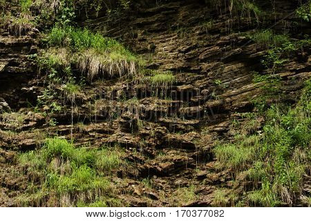 Photo rocky rocky slopes composed of laminated layers of stones and thickets of grass hanging