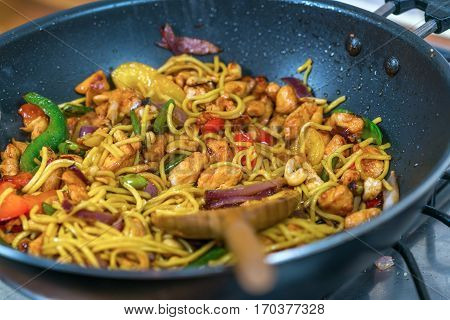 Preparing noodles with chicken and vegetables on the frying pan