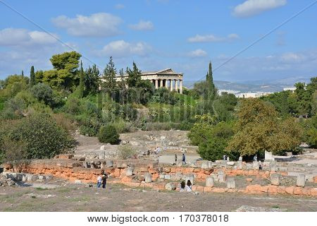 ATHENS, GREECE - OCTOBER 19: Tourists visit the Ancient Agora of Athens with Temple of Hephaestus OCTOBER 19, 2014 in Athens, Greece