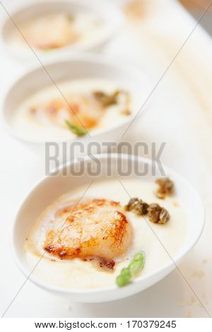 Grilled sea scallop with thick creamy sauce, close-up