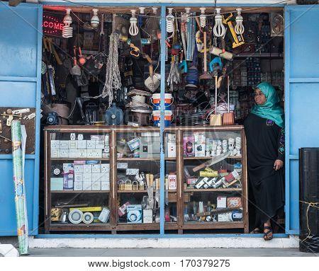Zanzibar, Tanzania - July 14, 2016: Small store selling lots of stuff in Zanzibar, Tanzania, local muslim woman as a seller
