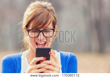 Girl thrilled with news from her smartphone.