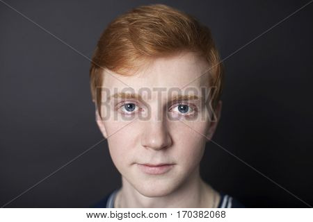 Portrait of red-haired handsome guy on a dark background in the studio. Closeup face