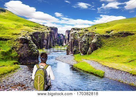 The elderly woman -  tourist with big backpack admiring the magnificent scenery. The concept of active northern tourism. The striking canyon in Iceland. Green Tundra in summer