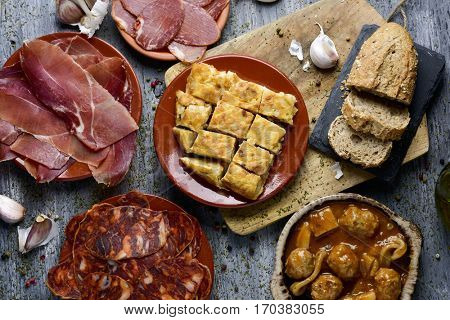 high-angle shot of some plates with an assortment of different spanish cold meats, such as serrano ham, chorizo or cured pork tenderloin, a spanish omelette and meatballs with cuttlefish, on a table