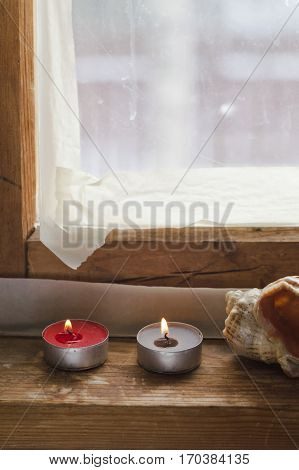 Sealing weather window tape on a wooden frame and home related objects placed on the window sill