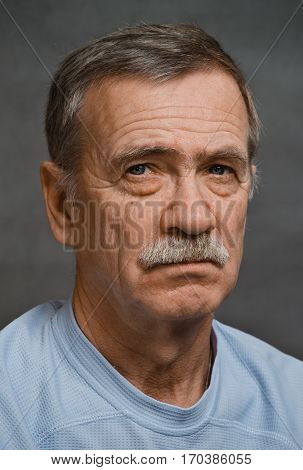 Closeup of a strict older man turned his piercing gaze directly into the camera.