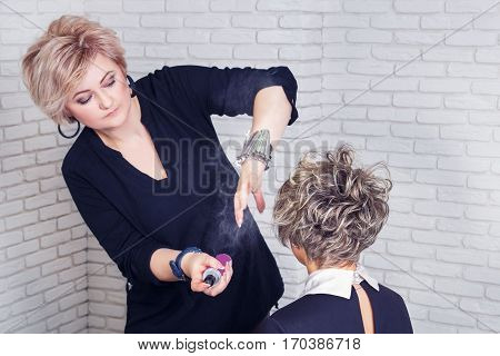Hairdresser with hair spray fixating hairdo at salon. Stylist using hairspray on client's hairstyle.  Master makes hairstyle using spray lacquer fixing . Spraying dynamic photo