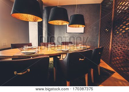 interior of restaurant with big lamps in golden light