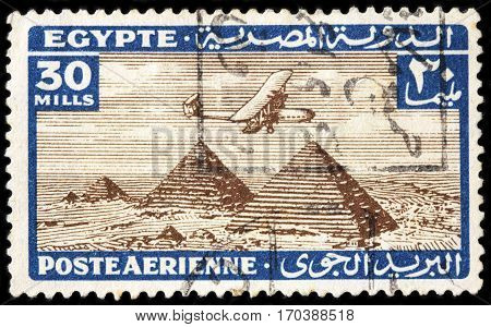 LUGA RUSSIA - FEBRUARY 7 2017: A stamp printed by EGYPT shows ancient aircraft flying over the Pyramids of Giza circa 1933