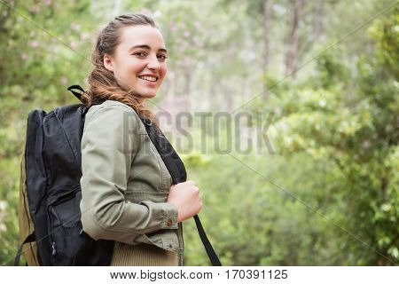 Smiling woman with backpack in the countryside