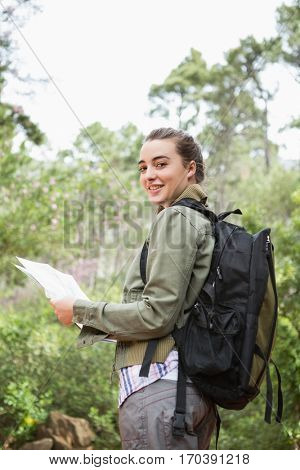 Smiling woman with backpack and map in the countryside