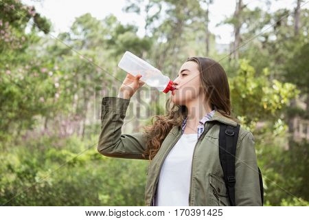 Woman drinking water with backpack in the countryside