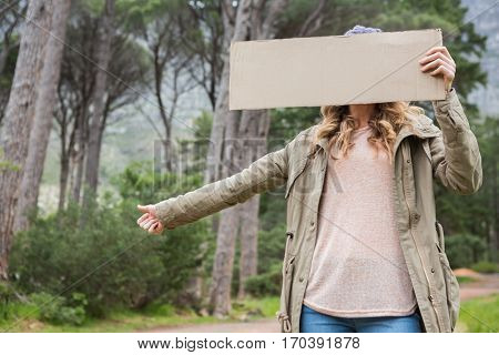 Hitch hiking woman holding cardboard in the countryside